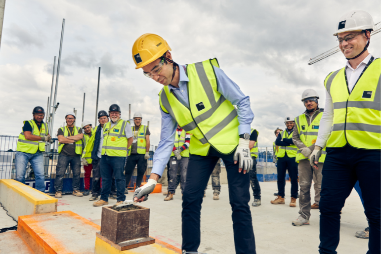 Karl Munslow Ong lays the final block of concrete